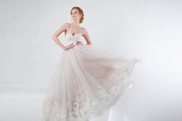 porträt eines schönen mädchens in einem brautkleid. braut in luxuriösen kleid auf weißem grund, die hände auf taille - verlobungskleider stock-fotos und bilder