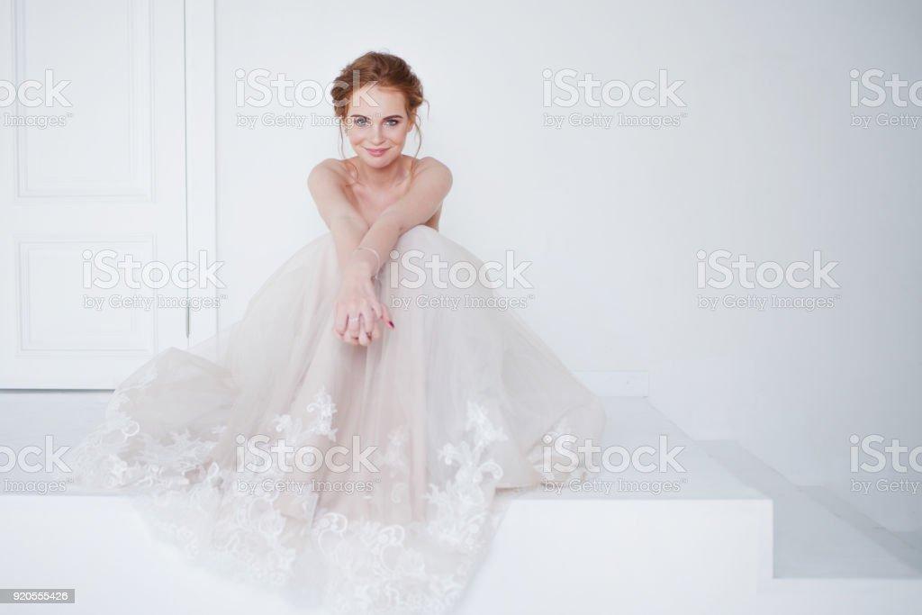 Retrato de una hermosa muchacha en un vestido de novia. Novia en lujoso vestido sentado en el suelo - foto de stock