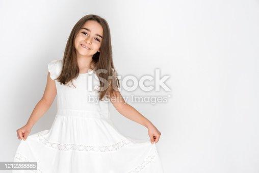 Cute little girl in white dress smiling on camera