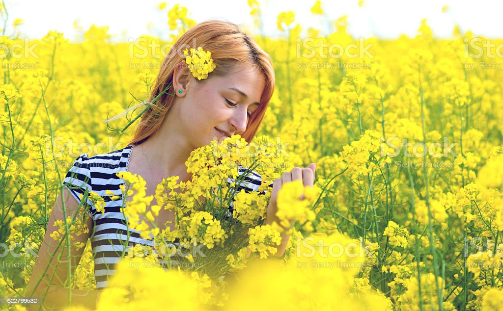 portrait of a beautiful girl in the colza field stock photo