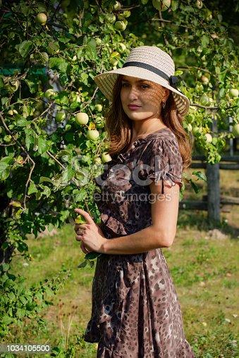 Portrait of a beautiful girl in a garden near an apple tree