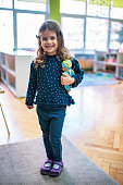 Portrait of a beautiful girl standing indoors and holding a doll.