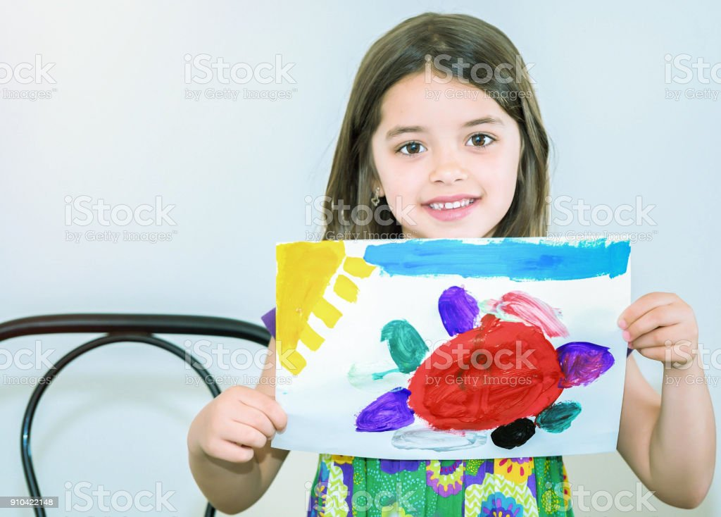 Portrait of a beautiful girl showing her drawing stock photo