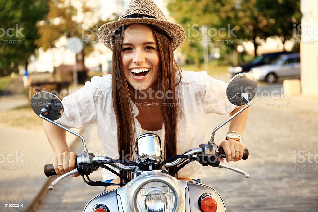 Portrait of a beautiful girl sitting on silver retro scooter stock photo