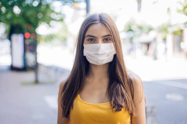 Portrait of a beautiful girl wearing a protective face mask stock photo