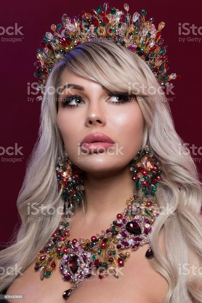 portrait of a beautiful girl with a crown on her head and ornaments on her chest stock photo