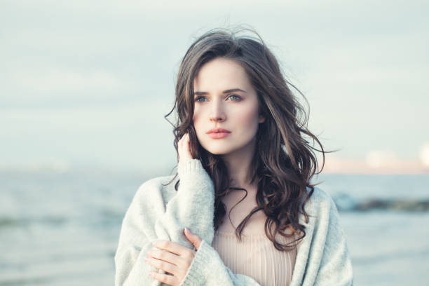 porträt eines schönen mädchens mit dem lockigen haar an einem kalten, windigen tag im freien - lustige augenbrauen stock-fotos und bilder