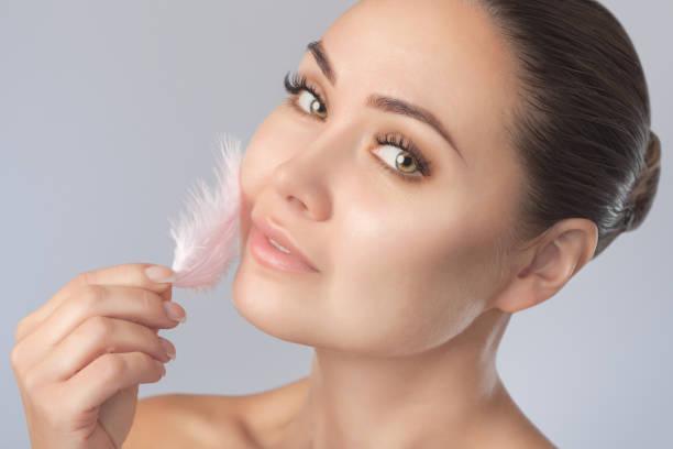 Porträt einer schönen glücklichen Frau mit sauberer Haut auf grauem Hintergrund. Sie hält eine rosa Feder neben ihrem Gesicht. Kosmetologie und Hautpflege. – Foto