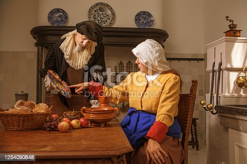 Portrait of a beautiful historical dutch milk maid and a nobleman wearing historically correct outfits in a typical townhouse kitchen