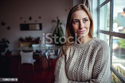 Portrait of a beautiful Latin woman. She is looking through the window
