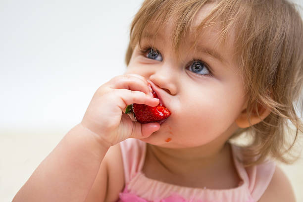 Portrait of a beautiful little girl with strawberry stock photo