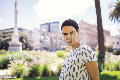 Beautiful mature woman enjoying a sunny day outdoors after work in a public park.