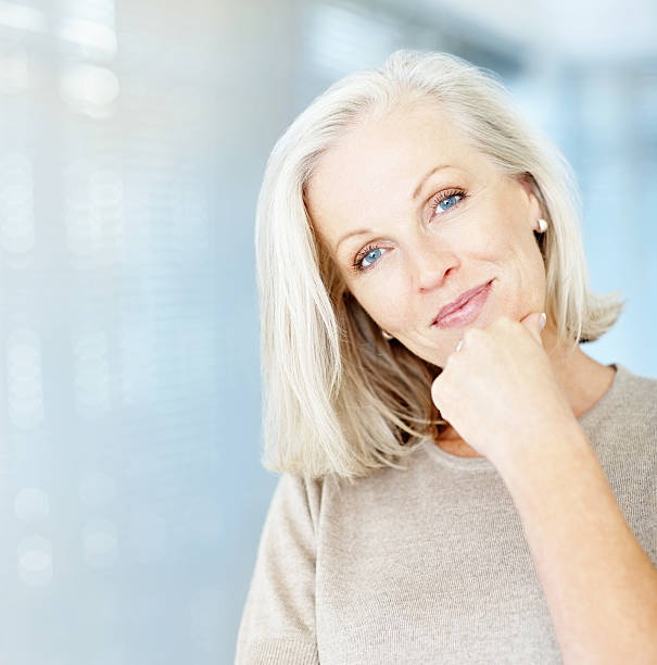 Portrait of a beautiful mature woman with hand on chin  only mature women stock pictures, royalty-free photos & images