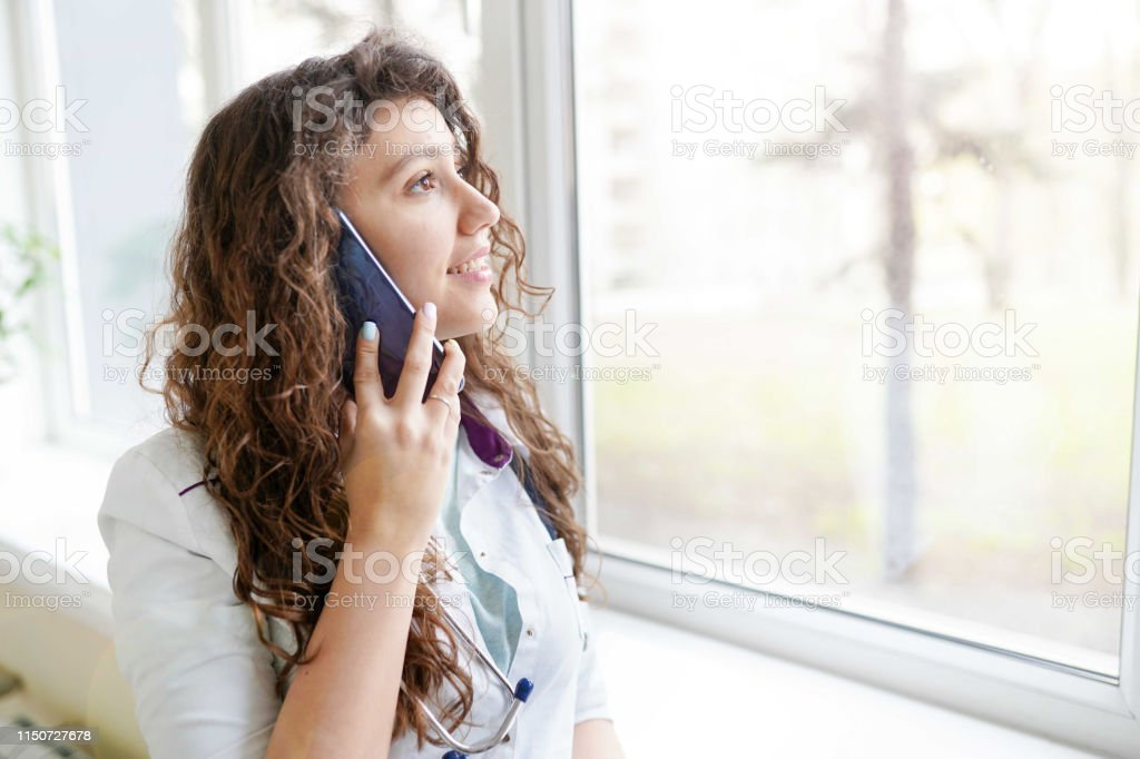 Portrait of a beautiful medical doctor talking on the phone. medical...