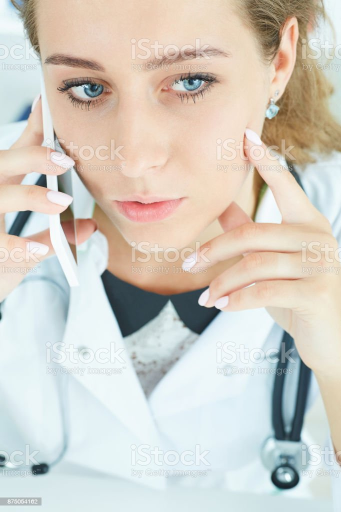 Portrait of a beautiful medical doctor talking on the phone.