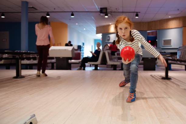 portrait of a beautiful redhead girl playing bowling - manonallard stock photos and pictures