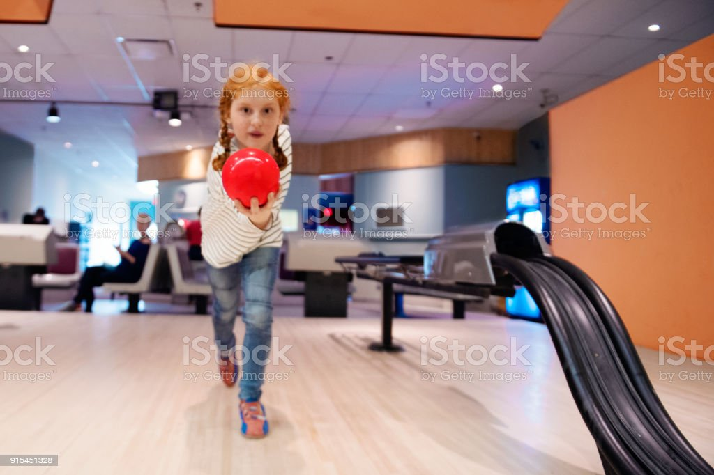 Portrait of a beautiful redhead girl playing Bowling stock photo