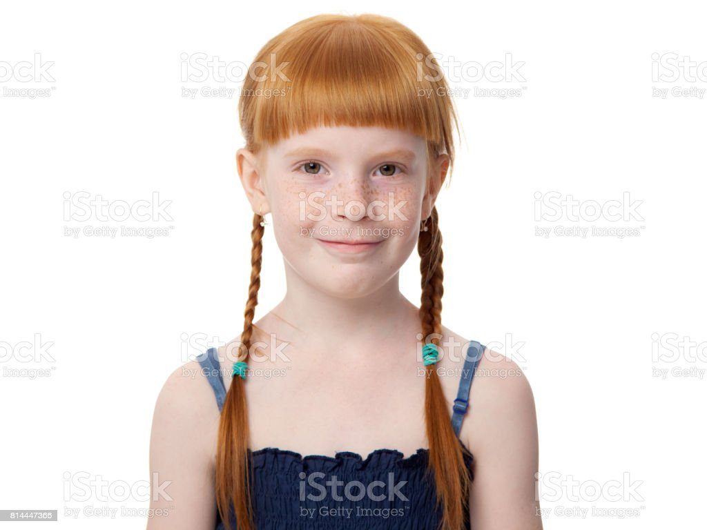 Portrait of a beautiful redhead joyful little girl in a blue dress on a white background stock photo