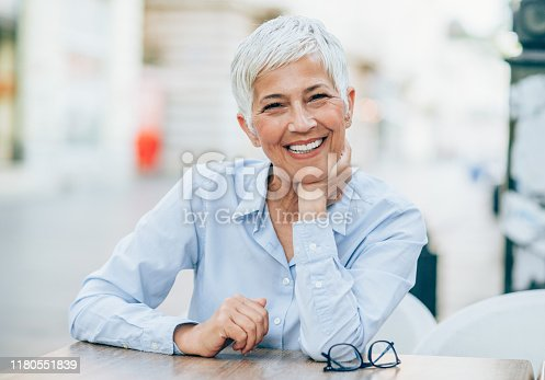 Happy mature woman sitting outdoor and looking at camera.