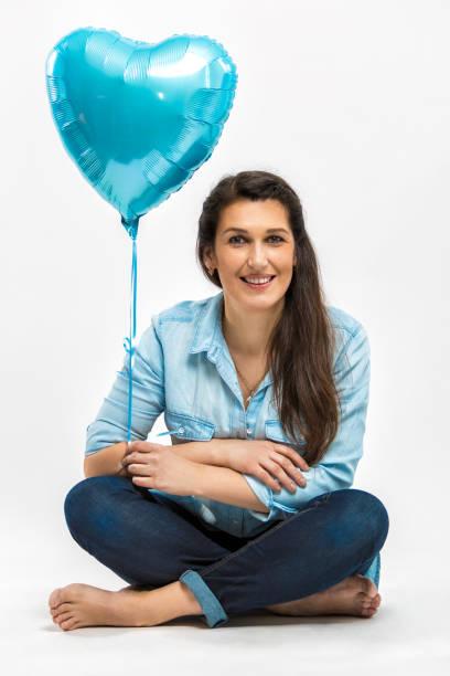 porträt einer schönen lächelnden erwachsenen frau mit einem blauen ballon in der form eines herzens. foto auf einem hellen hintergrund - ballonhose stock-fotos und bilder