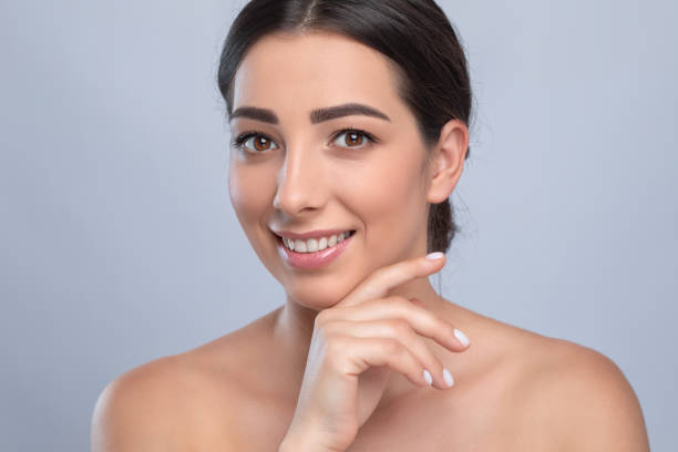 Portrait of a beautiful smiling brunette woman with naked shoulders, with clean skin and fresh make-up. Aesthetic cosmetology, hair treatment and makeup concept. stock photo