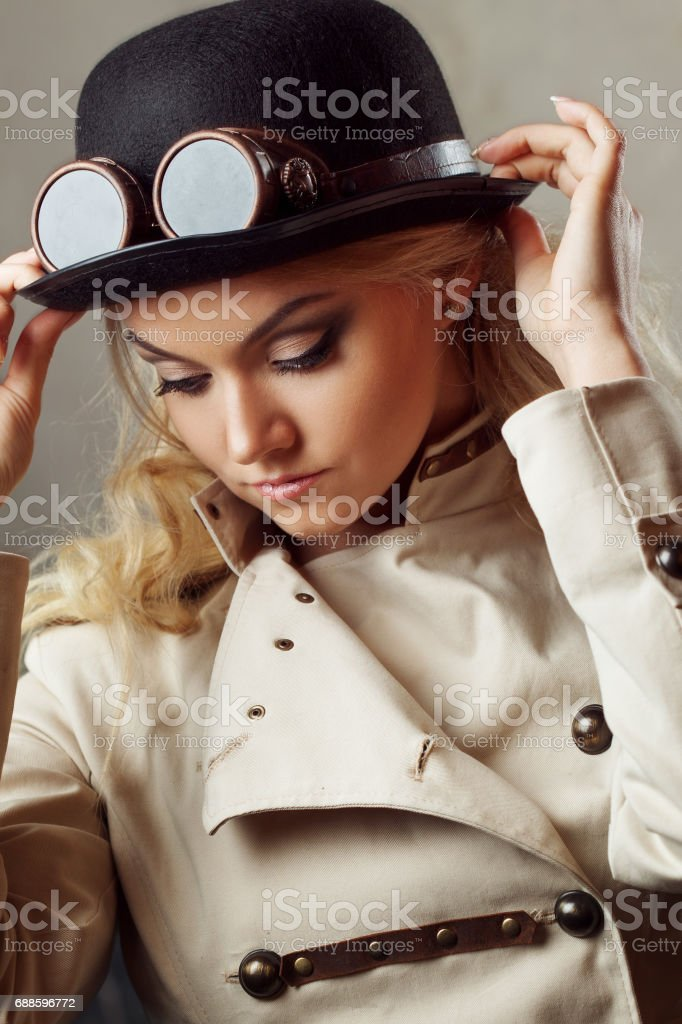78b0c1cdc2a Portrait of a beautiful steampunk woman hat-bowler hat over grunge  background. royalty-