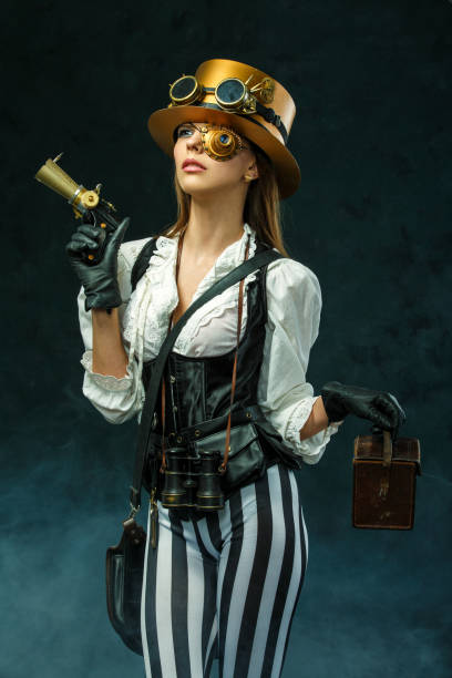 portrait of a beautiful steampunk woman holding a gun - steampunk fashion stock photos and pictures