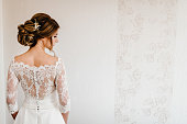 istock Portrait of a beautiful stylish bride with an elegant hairstyle view from the back. Wedding, people, fashion and beauty concept - bride in wedding dress. Back view. 1213809785