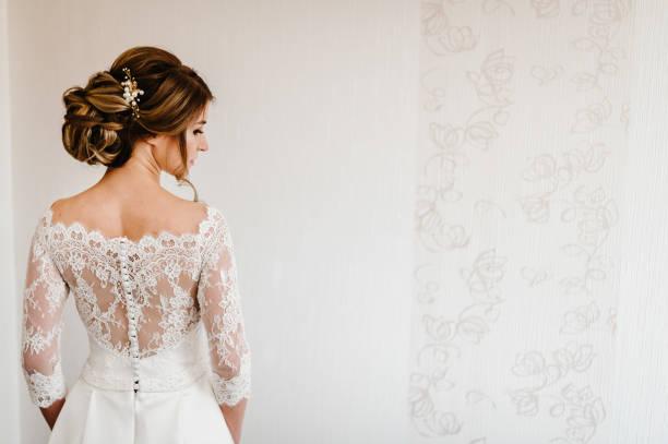 portret pięknej stylowej panny młodej z eleganckim widokiem fryzury z tyłu. ślub, ludzie, koncepcja mody i urody - panna młoda w sukni ślubnej. widok z tyłu. - panna młoda zdjęcia i obrazy z banku zdjęć