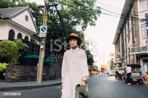 A portrait of a beautiful Asian woman dressed in white vintage clothes walking down the street.