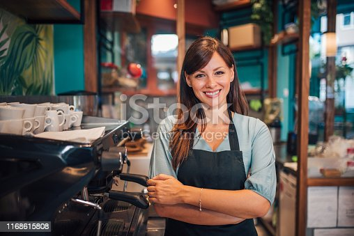 Portrait of a beautiful waitress wearing an apron, smiling at camera.