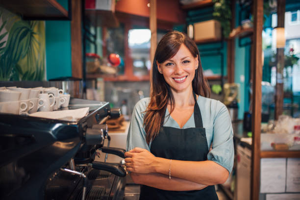 Portrait of a beautiful waitress wearing an apron, smiling at camera. Portrait of a beautiful waitress wearing an apron, smiling at camera. barista stock pictures, royalty-free photos & images