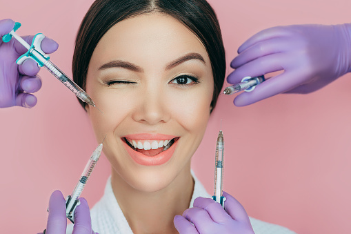istock Portrait of a beautiful winking woman and many syringes with beauty injections around her face 1173342078