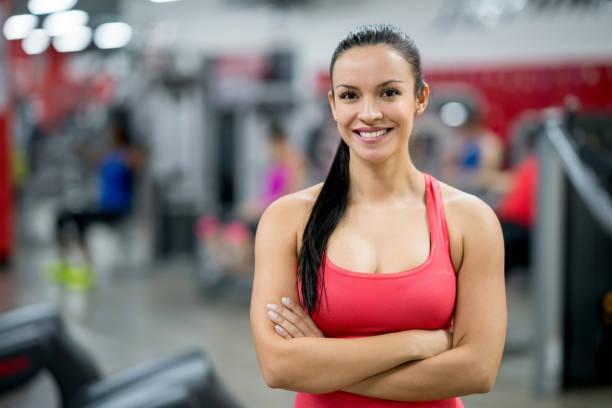 retrato de una mujer hermosa en el gimnasio - entrenador personal fotografías e imágenes de stock