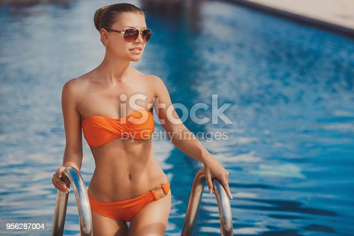 Beautiful young woman - brunette hair tied back, wearing sun glasses in an orange bikini posing for a photograph holding silver railings, pool with blue water.
