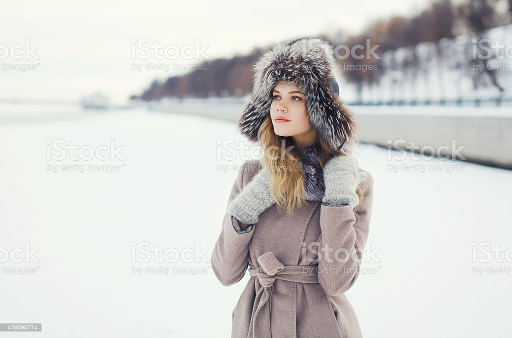 Portrait of a beautiful woman dressed coat and fur hat stock photo