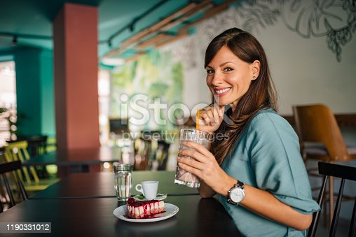 Portrait of a beautiful woman enjoying in the cafe, smiling at camera