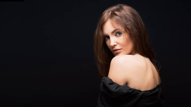 portrait of a beautiful woman in a dark dress posing on a dark background, beautiful brown hair looking from shoulder stock photo