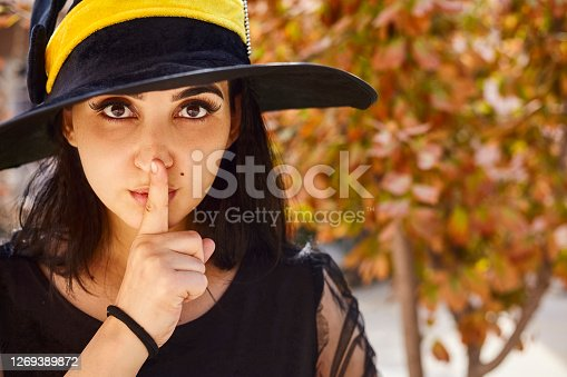 Portrait of beautiful female in witch hat sticking out her tongue and showing quiet sign. Attractive woman with little secrets showing silence gesture