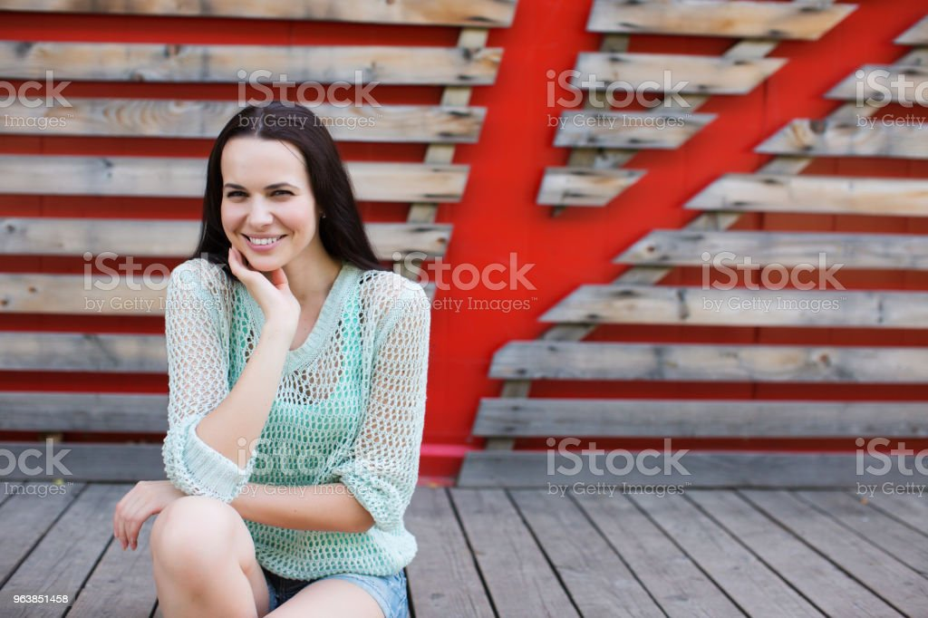Portrait of a beautiful woman in denim shorts sitting on a wooden background. - Royalty-free Adult Stock Photo