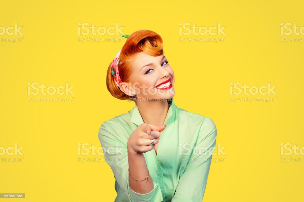 portrait of a beautiful woman pinup retro style pointing at you smiling laughing isolated yellow background wall. Body language, gestures, psychology. stock photo