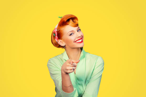 portrait of a beautiful woman pinup retro style pointing at you smiling laughing isolated yellow background wall. Body language, gestures, psychology. - Photo