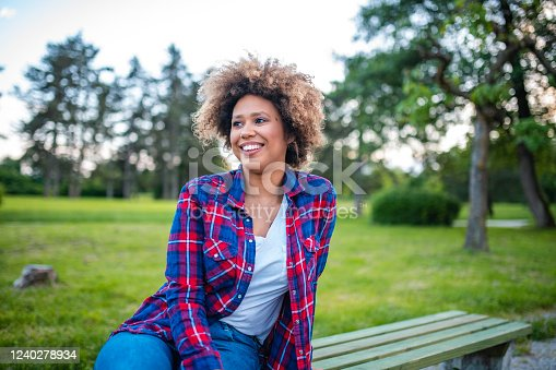 Portrait of a beautiful woman sitting on the bench in a park and smiling