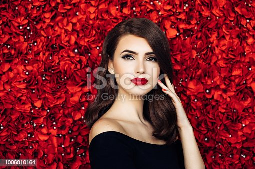 Portrait of a beautiful woman standing against floral pattern