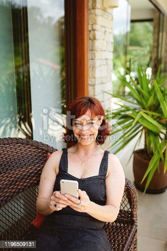 825083304 istock photo Portrait of a beautiful woman using cell phone and looking at camera 1196509131