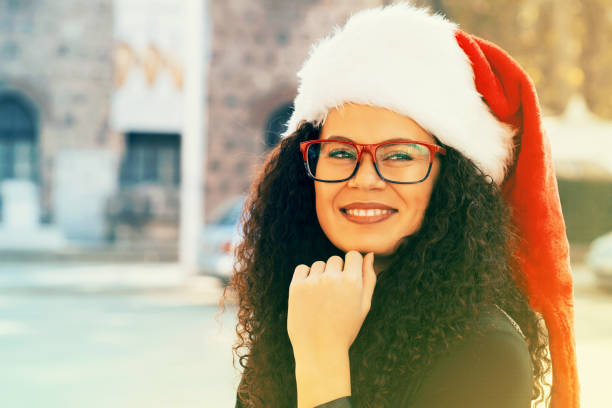 Portrait of a beautiful woman wearing santa hat stock photo