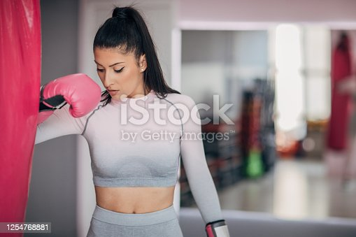 Portrait of a fit young woman with boxing gloves and punching bag in the gym.