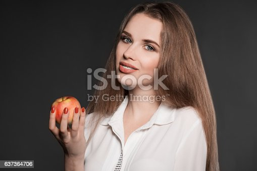 istock Portrait of a beautiful woman with braces on teeth and 637364706