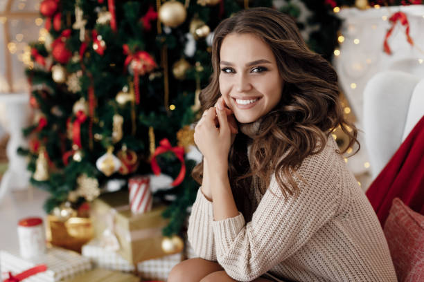 Portrait of a beautiful woman with curls at the Christmas tree with gifts of new year lights garland Young beautiful woman near elegant Christmas tree with gifts alone waiting for Christmas. Portrait of a beautiful girl on New year's eve.Christmas interior in the background.Young and beautiful woman celebrating Christmas at home alone. beautiful woman stock pictures, royalty-free photos & images
