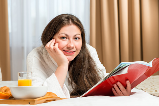 683349444 istock photo portrait of a beautiful woman with  magazine in the room 478437782